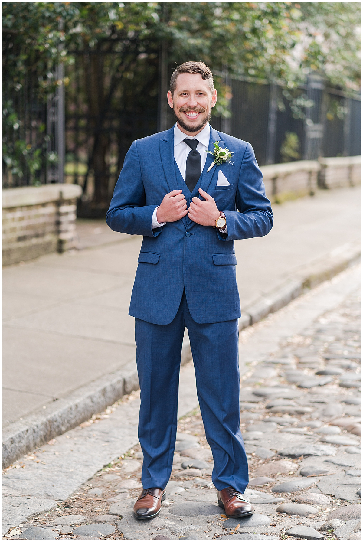 groom in navy suit holds lapels standing on cobblestone road