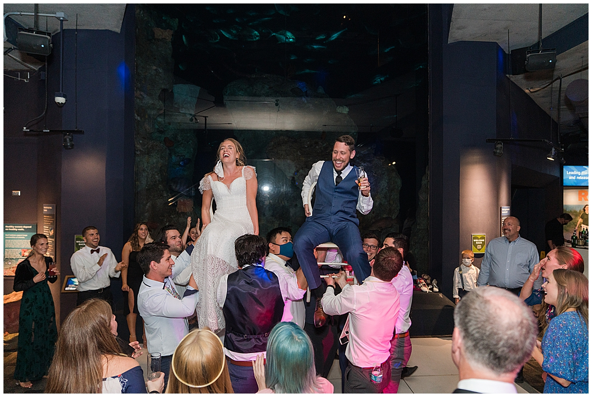 bride and groom lifted in chairs at Charleston Aquarium Wedding reception