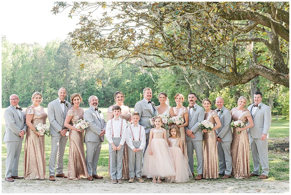 bride and groom pose with bridal party in grey and rose gold attire
