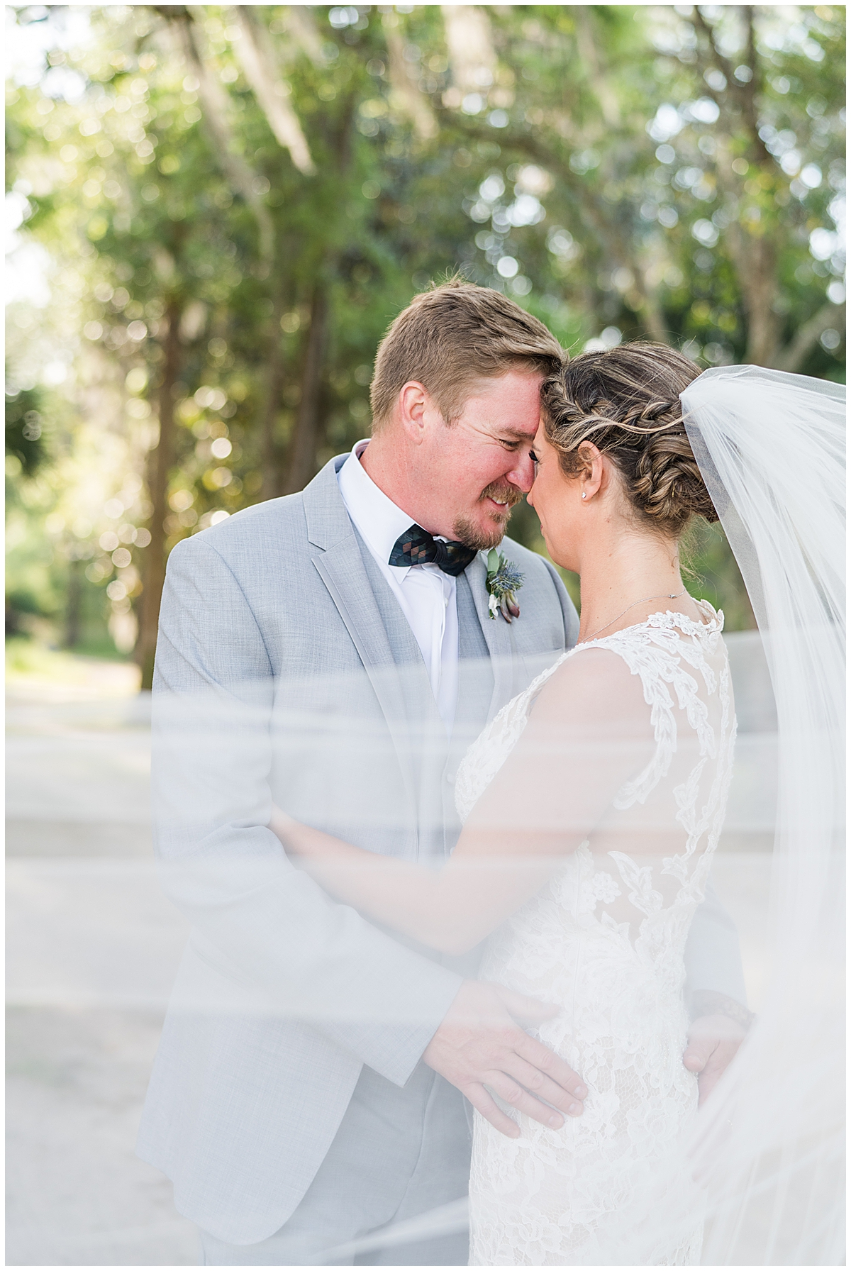 bride and groom stand nose to nose with veil wrapped around their shoulders