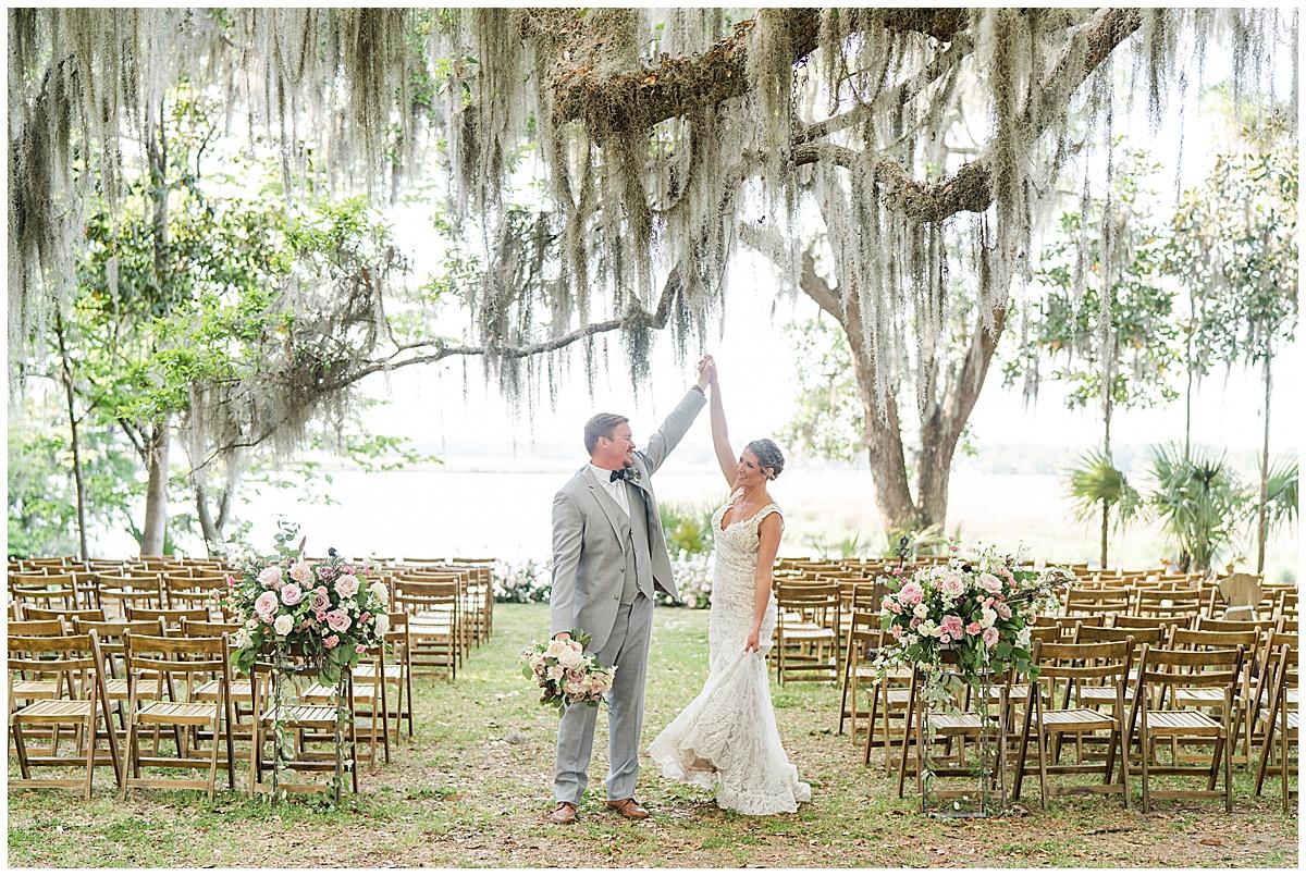 groom twirls bride during Runnymeade Plantation Charleston wedding portraits