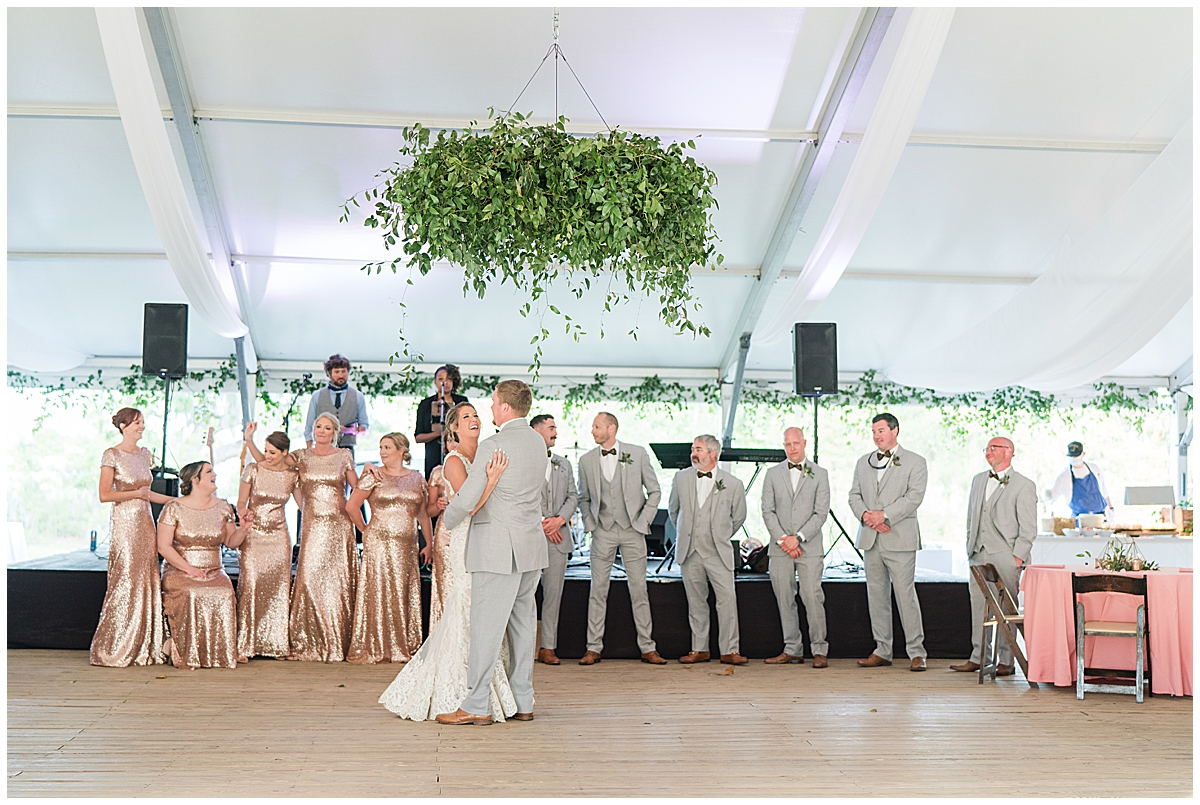 bride and groom dance during wedding reception surrounded by bridal party