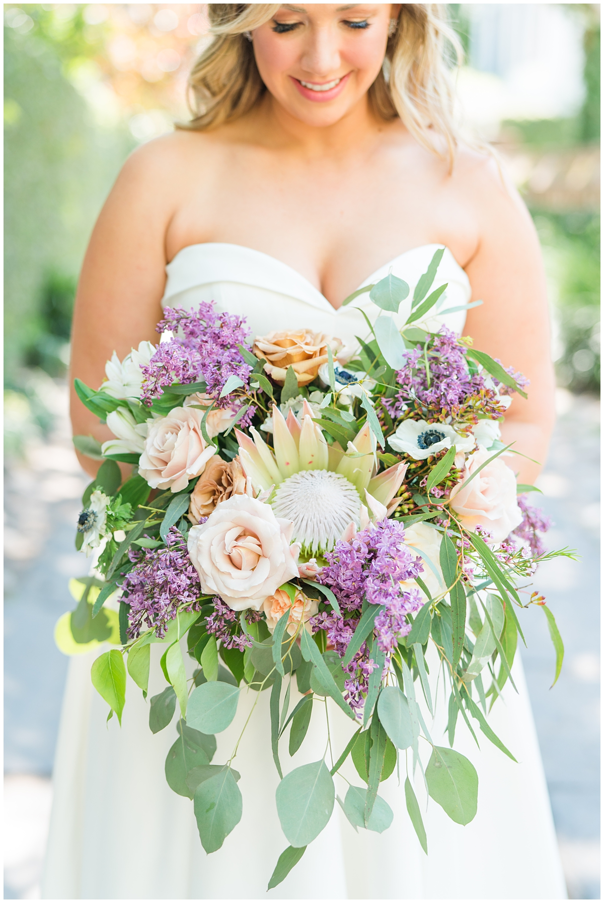 bride holds bouquet with pink and purple flowers