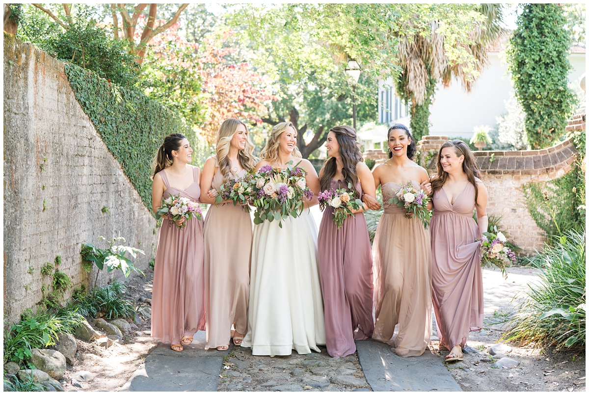 bride and bridesmaids in pink gowns walk downtown in Charleston
