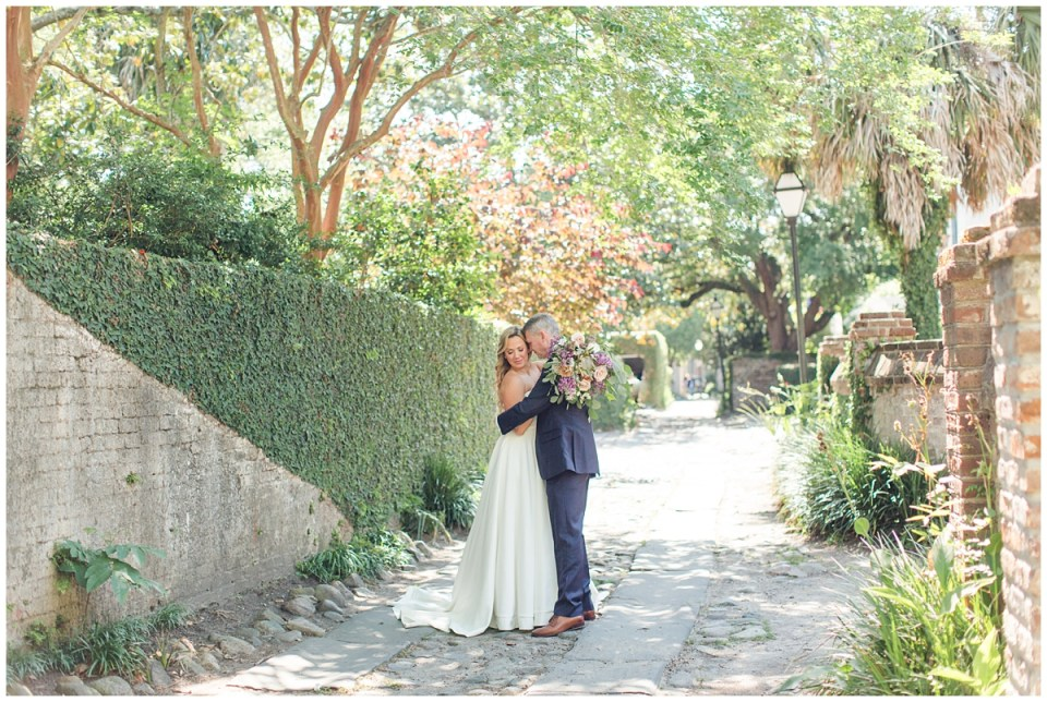 bride and groom hug on cobblestone road in Charleston