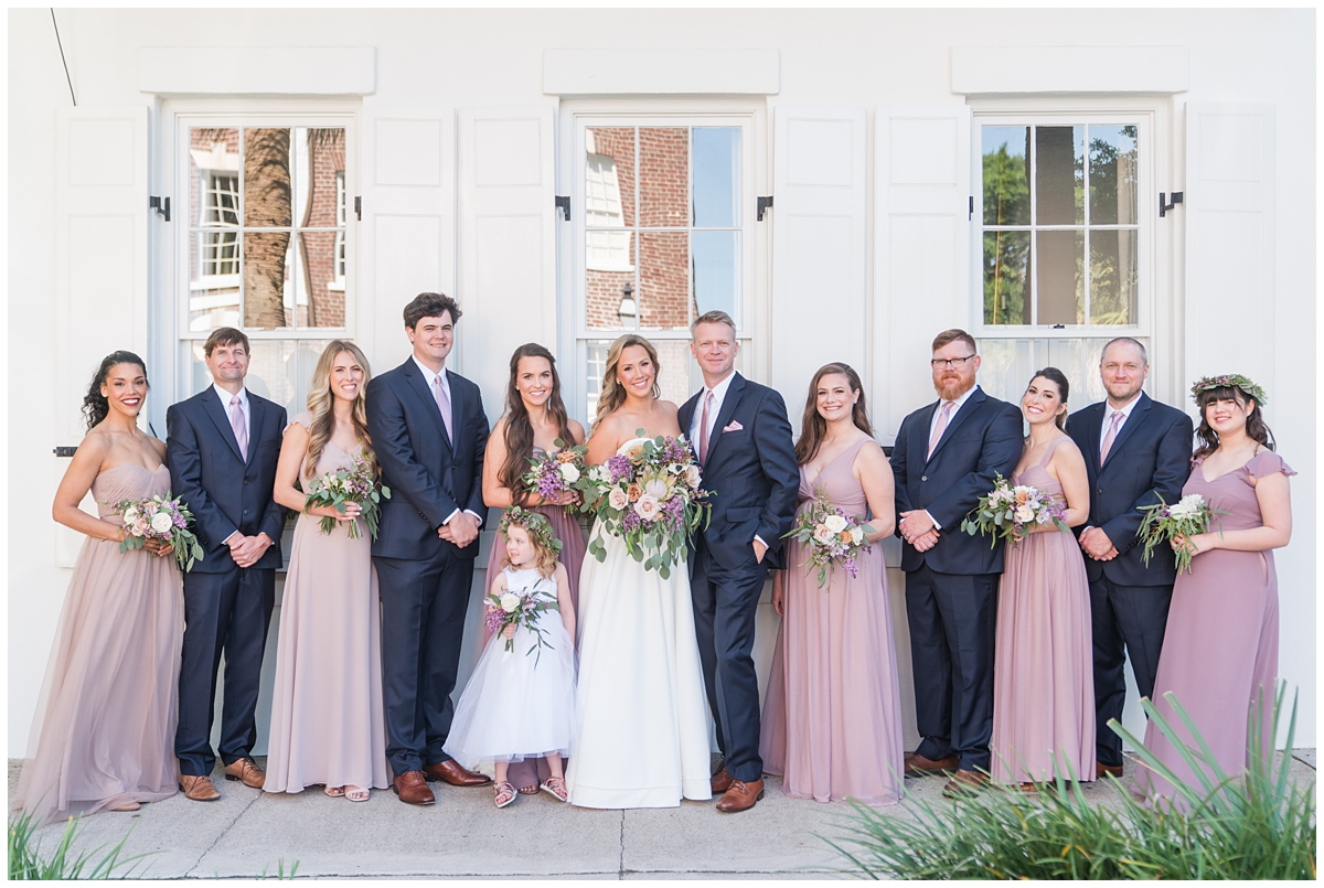 bride and groom pose with bridal party by White House in Charleston SC