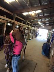 Horse and Rider hugging in the barn aisle