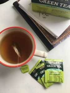 Cup of bigelow tea with tea bags and books