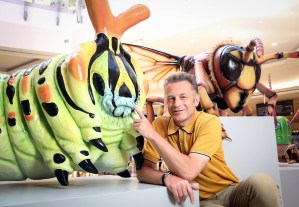 Chris Packham interacts with a 7ft long lifelike model of a Swallowtail Caterpillar and a Hornet at the launch of Big Bugs on Tour at intu Lakeside