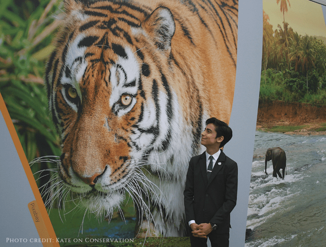 Aidan Gallagher next to tiger banner at illegal wildlife trade conference 2018