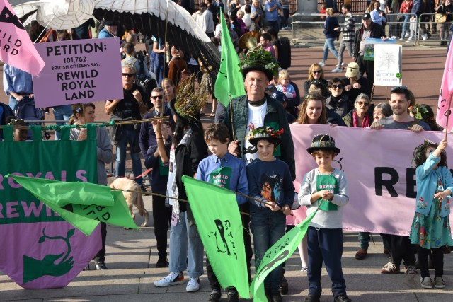 Chris Packham stands with children on the royal rewild procession outside Buckingham Palace