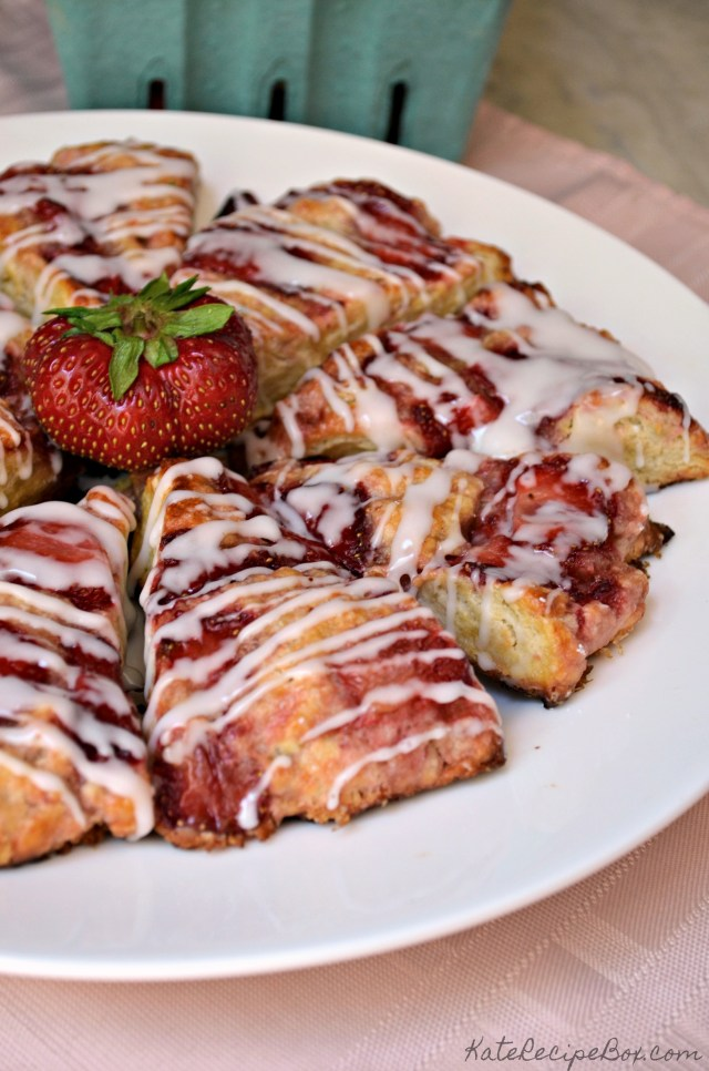 Eight strawberry scones drizzled with  icing arranged in a circle on a white plate. The plate is sitting on a pink napkin. A red, ripe strawberry sits on top of the scones.