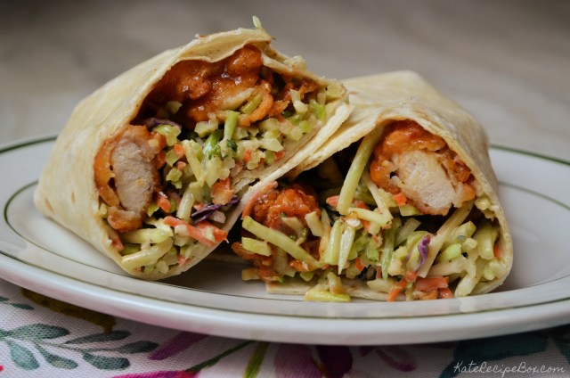 Cross-section view of a wrap stuffed with barbcue sauce-covered chicken tenders and broccoli slaw.