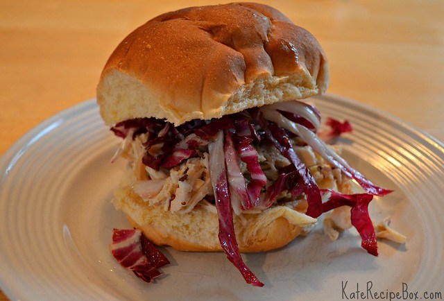 Pulled chicken in a honey mustard sauce on a roll along with a slaw of red cabbage.