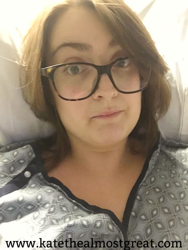 Kate lies in a hospital bed. She is a white woman with brown hair. She wears large brown glasses and a hospital gown.