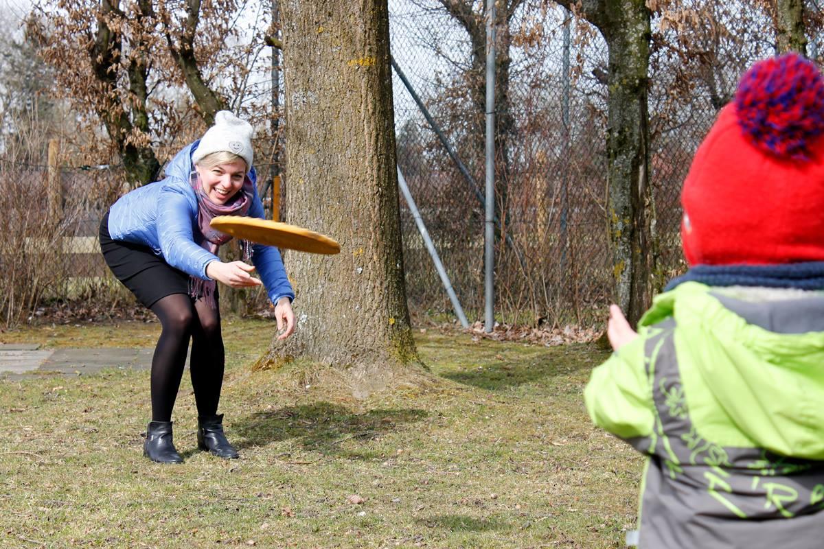 Katharina Schulze spielt Frisbee im Garten der KiTa Wawuschel