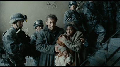 Screen shot of characters from the movie Children of Men as they seek protection from military soldiers