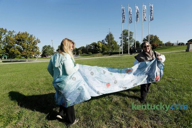 """Flag artist Kathleen O'Brien, right, and friend Laura Sullivan showed what one her flags looks like up close after a press conference unveiling flags """"Blazing"""" the Legacy Trail at Lexmark near the Legacy Trail in Lexington, Ky., on Oct. 13, 2015. Photo by Pablo Alcala 