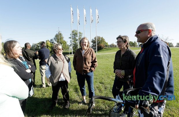 """From left, project organizer Kate Sprengnether, left and artists including Kathleen O'Brien, Janice Durham, Mary Rezny, and Don Ament gathered near flag designed by fellow artist Jim Eichner (back to camera) after a press conference unveiling flags """"Blazing"""" the Legacy Trail at Lexmark near the Legacy Trail in Lexington, Ky., on Oct. 13, 2015. Photo by Pablo Alcala 