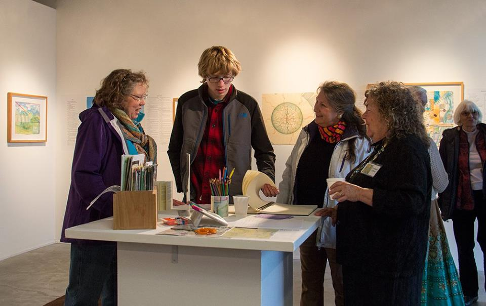 Jan Durham and others enjoy looking at the community journal, photo credit Melissa Hall
