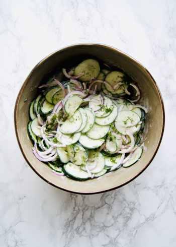 Creamy greek yogurt cucumber salad in a large bowl on a marble countertop