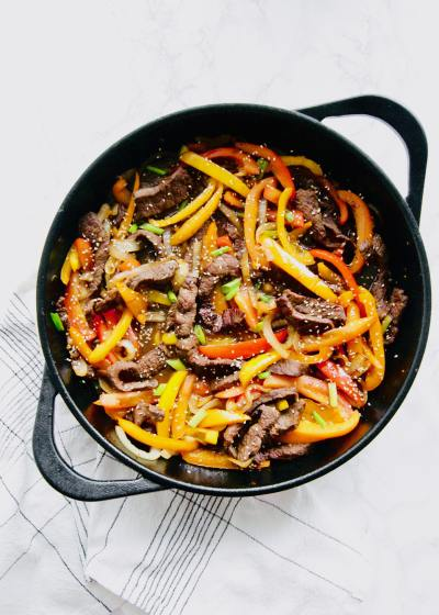 Beef, peppers, and onions in a cast iron skillet