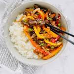 Seared beef, stir fried peppers and onions, and all tossed together with an easy homemade Korean stir fry sauce. An easy dinner that that tastes even better than takeout! Ready in under 30 minutes! Recipe at KathleensCravings.com #KathleensCravings #stirfry #koreanbeef #ricebowls #stirfrysauce #peppersandonions #30minutemeal