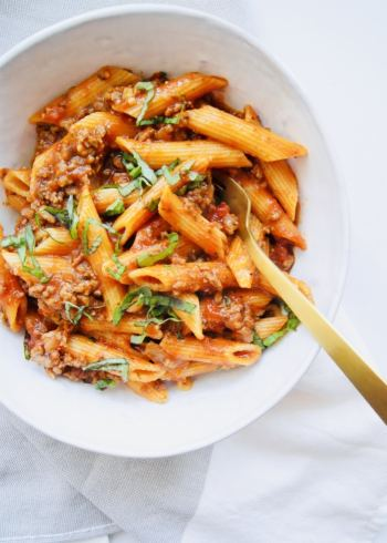 Penne Bolognese in white bowl with gold fork