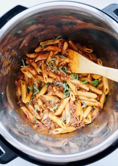 close up of penne bolognese in instant pot with wooden spoon