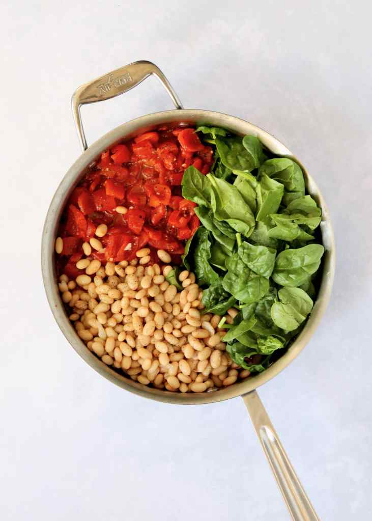 Tomatoes, spinach, and white beans in sauté pan