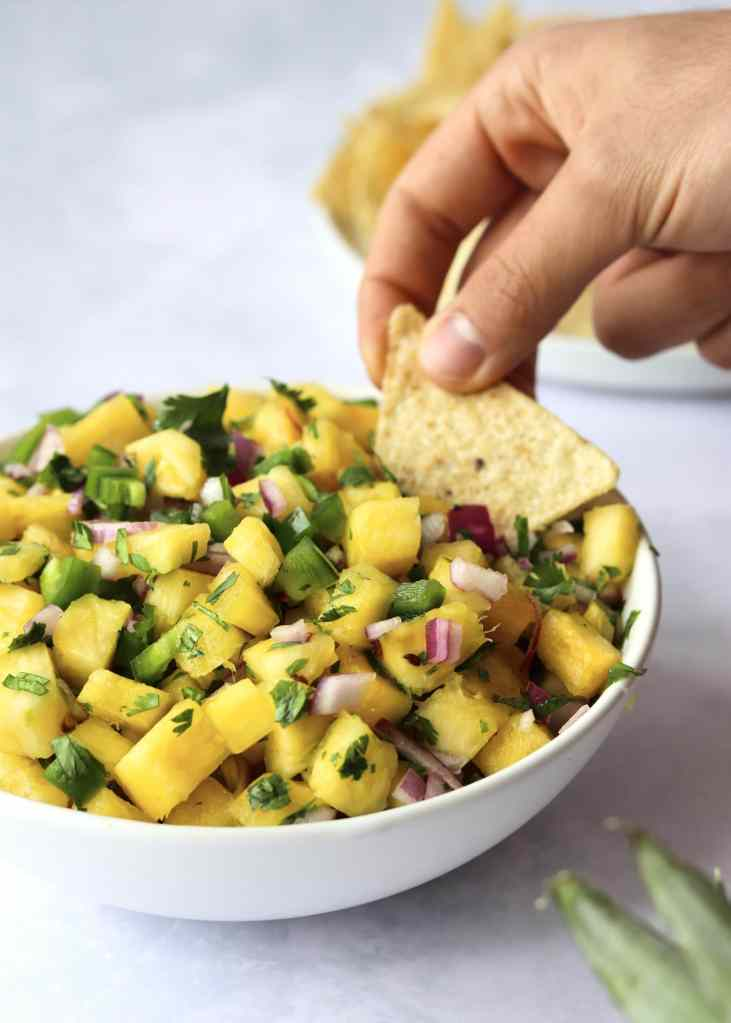 Hand dipping tortilla chip into pineapple salsa