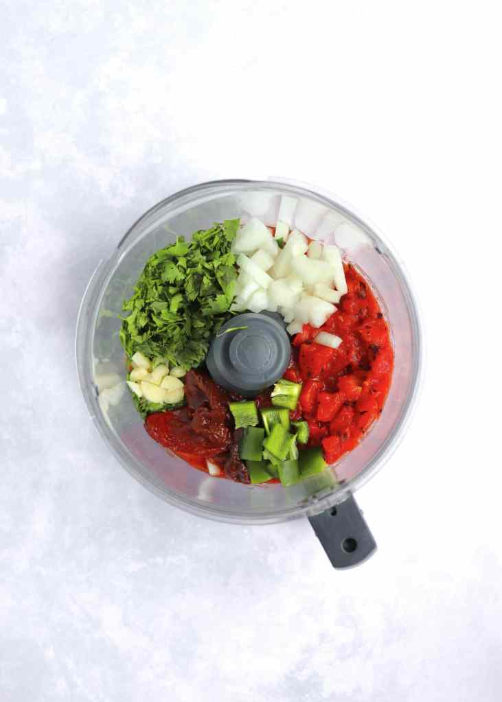Tomatoes, chipotle pepper onion, cilantro, jalapeno, and garlic in food processor.