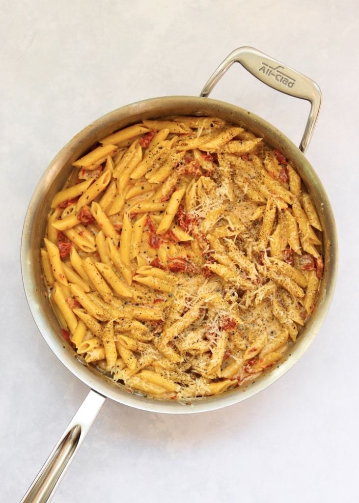 Creamy pasta in pan with parmesan cheese on top
