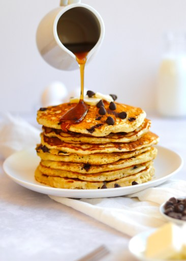 Maple syrup being poured on a stack of fluffy chocolate chip pancakes