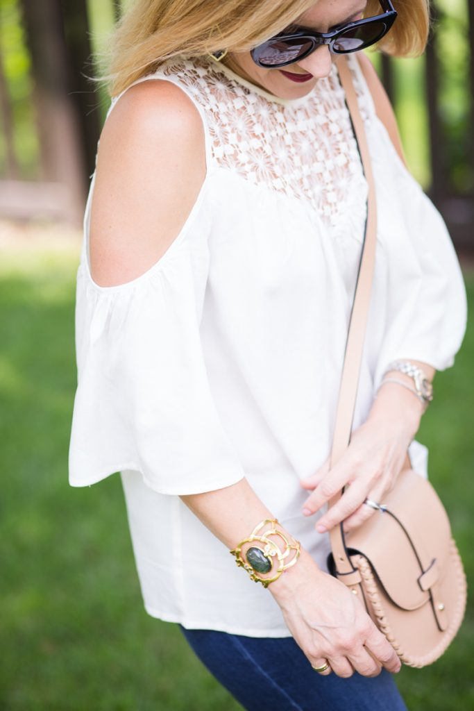 A white cold shoulder top with Julie Vos cuff and tan saddle bag