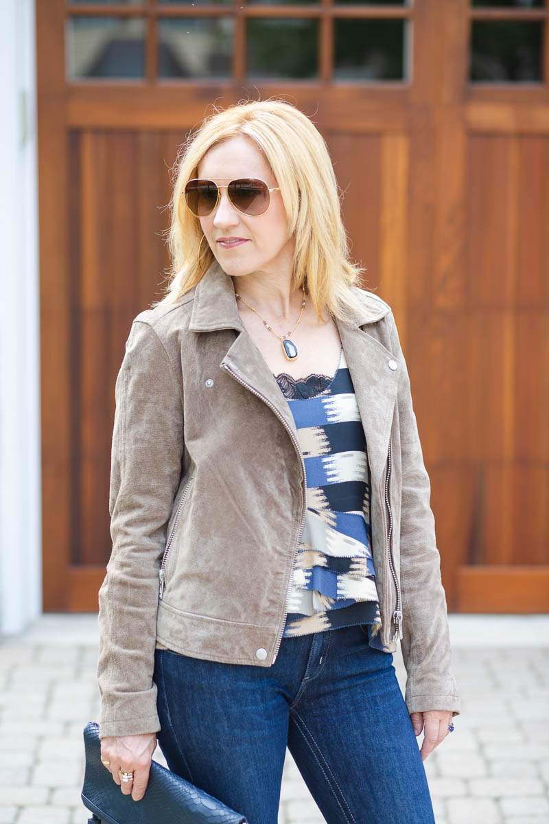 Suede moto jacket with a printed tank and flared jeans.