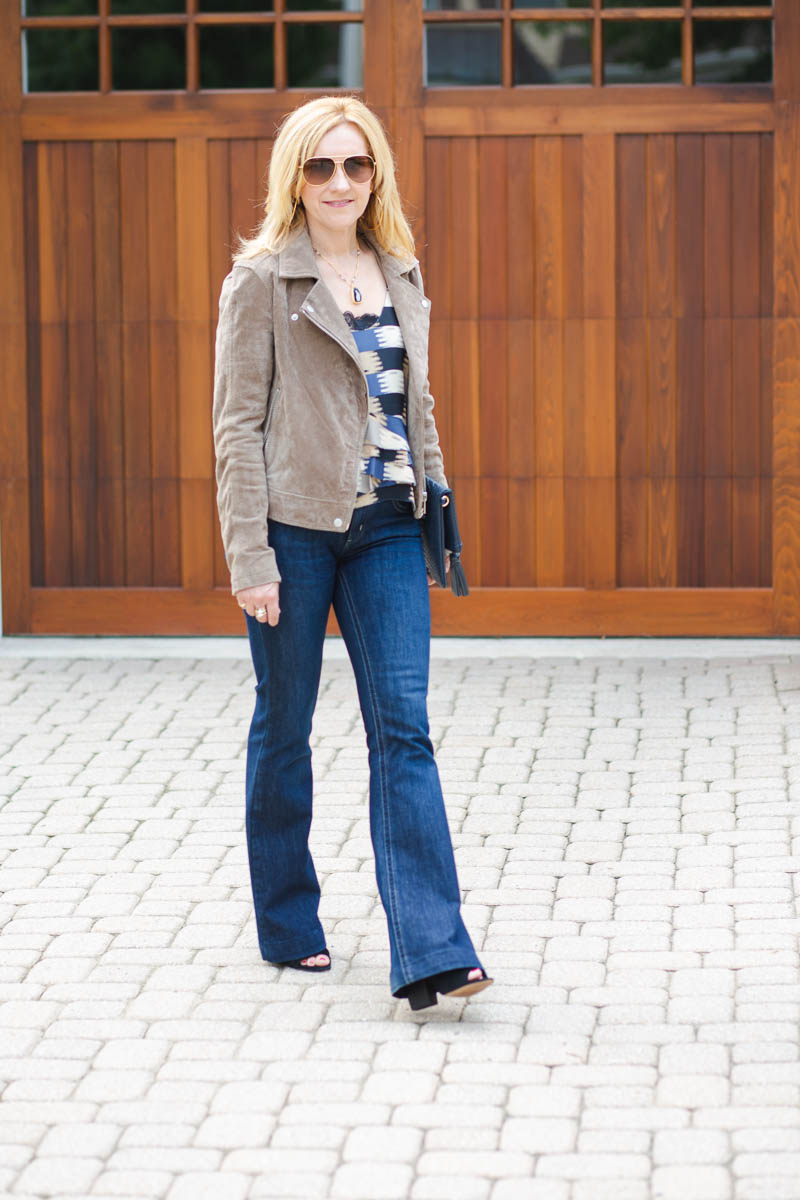 Edgy chic look featuring a suede moto jacket and flared jeans.