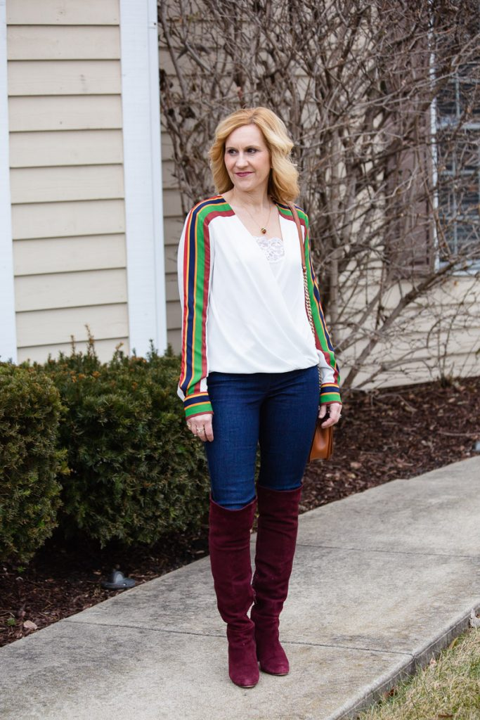 Casual chic look featuring sporty stripes, skinny jeans, and over the knee boots.