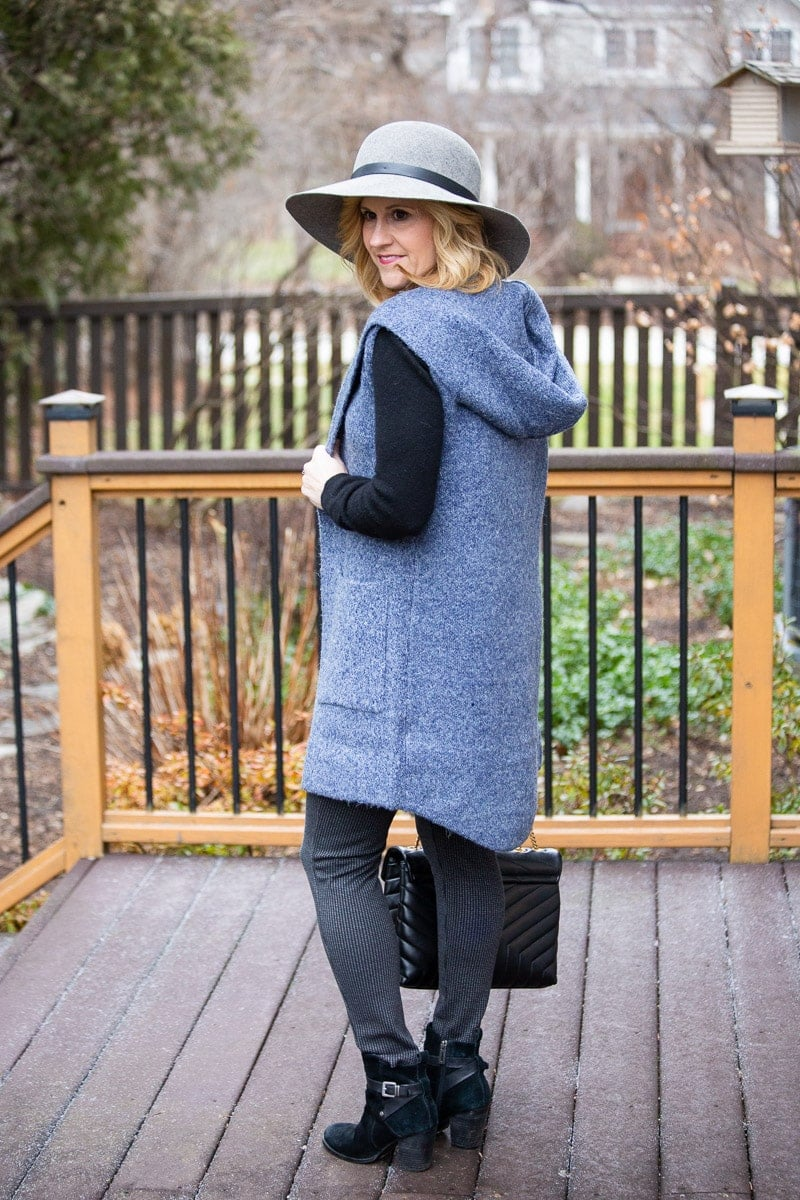 Blue hooded long vest paired with a black cashmere sweater and printed leggings.