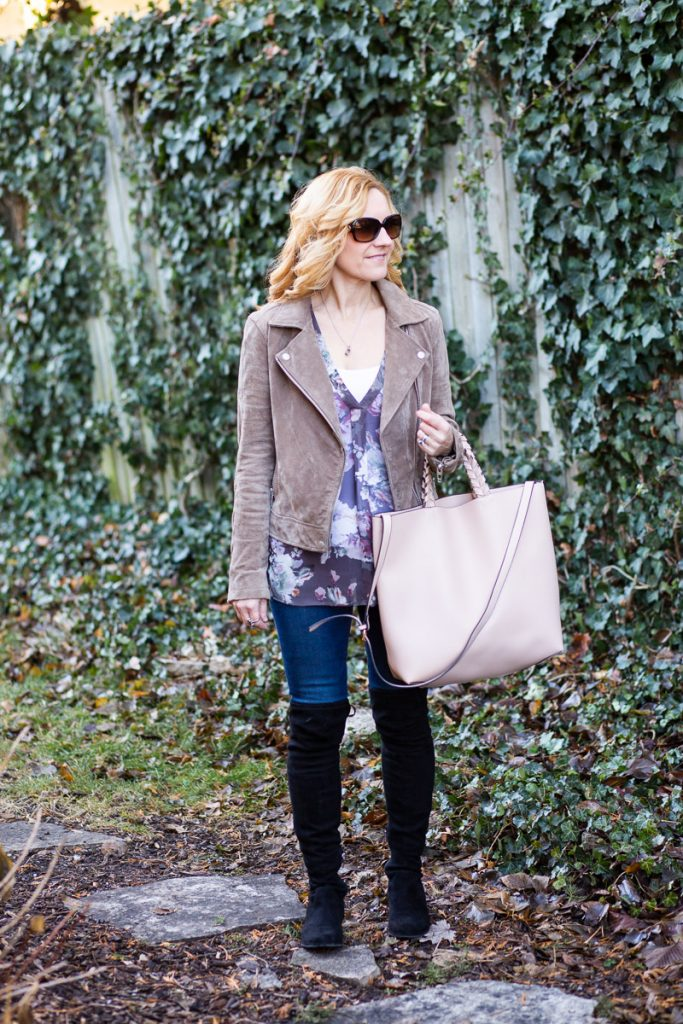 A winter outfit featuring a floral top and suede jacket with a vegan tote bag.