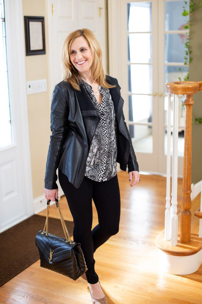 Wearing an all black look that features a chic snakeskin top.