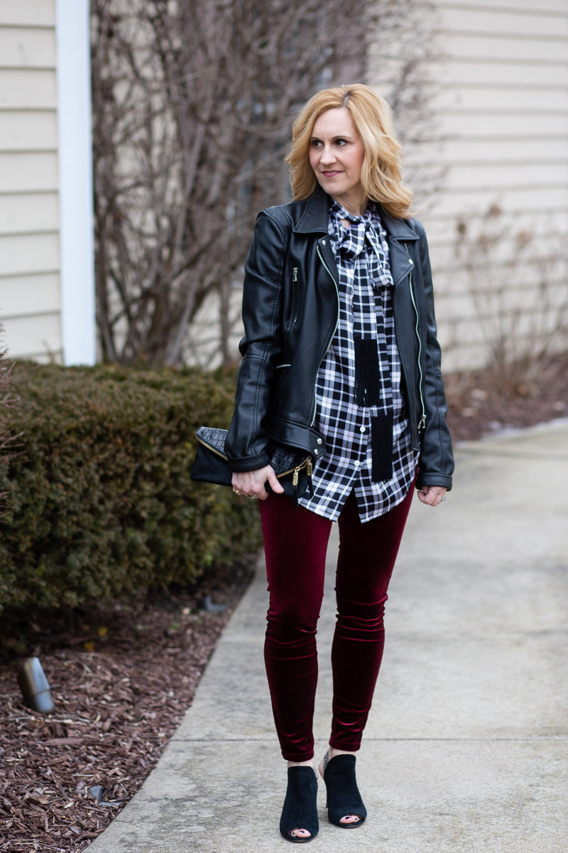 Styling a black and white plaid blouse with a moto jacket and velvet leggings for a edgy cool night out look.