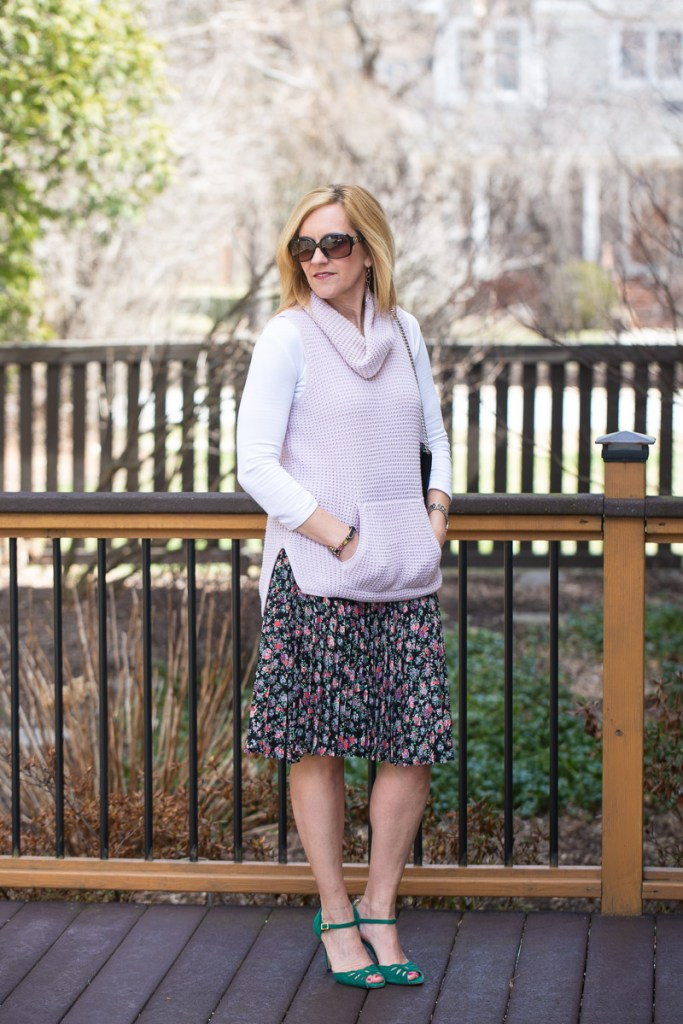 Pink sweater vest paired with a floral pleated skirt.