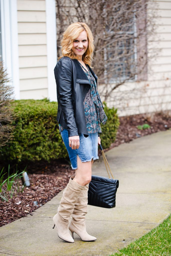 Styling a black leather jacket with a denim pencil skirt and beige suede slouchy knit boots.
