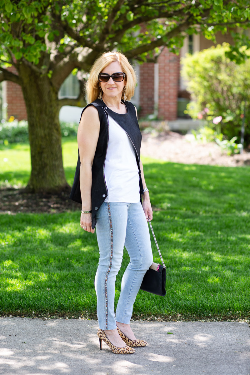 Edgy summer outfit featuring a black vest and skinny jeans with side stripes.