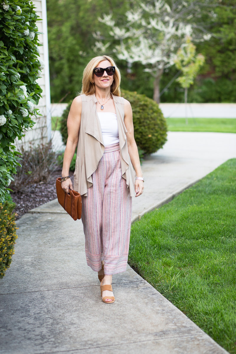 A summer chic outfit featuring striped palazzo pants, bandeau top, and draped vest.