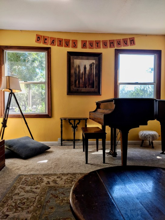 """Golden yellow living room with """"Beatus Autumnum"""" banner"""