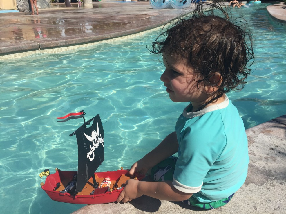 toddler boy wearing teal coloured rash guard sits on the edge of the lazy river with a toy pirate ship in his hands at Beaches Turks and Caicos Resort