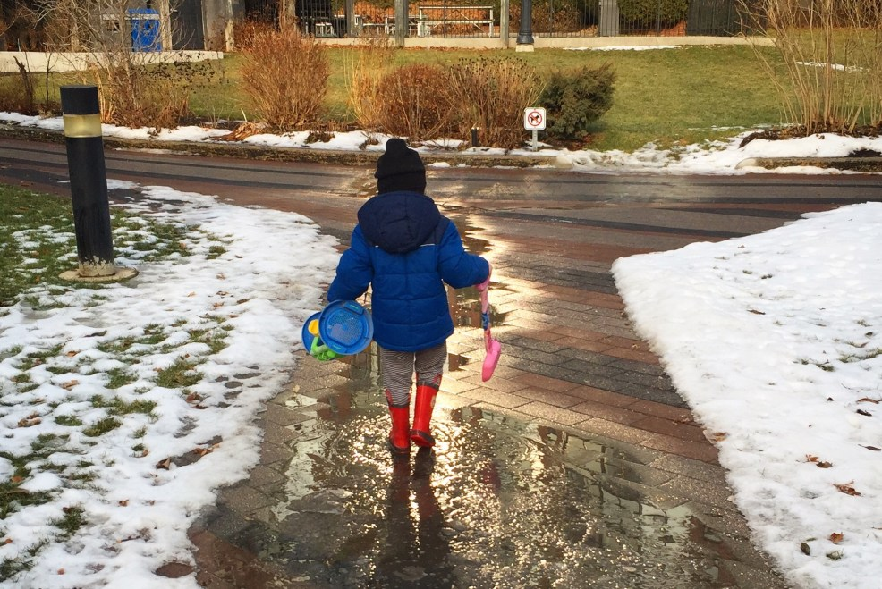 boy wearing a blue jacket walking through the puddle to play in the city of toronto