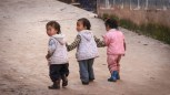 Three toddlers hold hands as they walk uphill in the small town we visited.